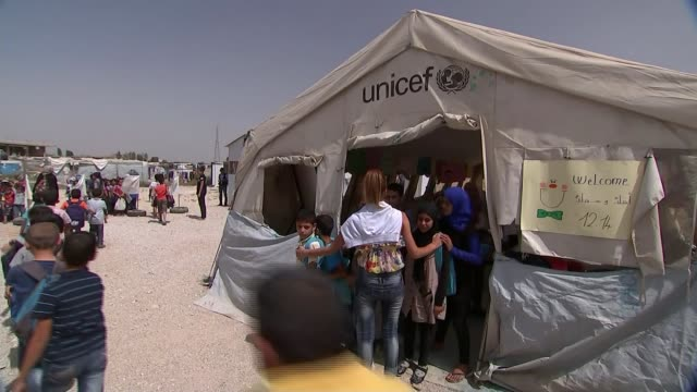 large influx of syrian refugees children along past 'unicef' tent low angle view children along waving and saying 'bye' sot - unicef stock videos & royalty-free footage