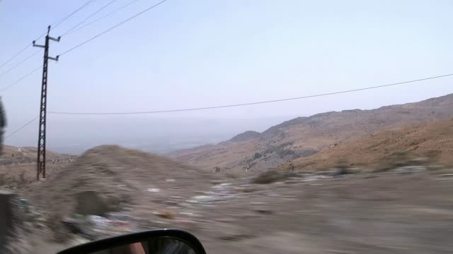 S POINT OF VIEW along road TRACKING SHOTS through car window on road from Beirut towards Beqaa valley Beqaa Valley EXT Zahle Refugee camp makeshift...