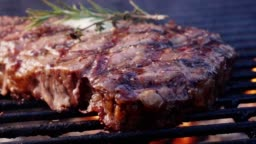 Large Juicy Beef Rib Eye Steak on a Hot Grill with Charcoal and Flames