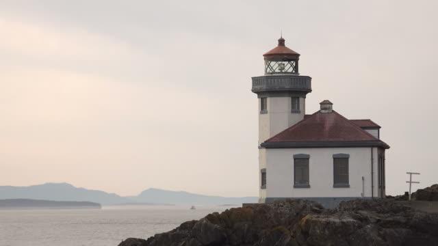 Large Lighthouse on Rocky Shoreline Under Sunset