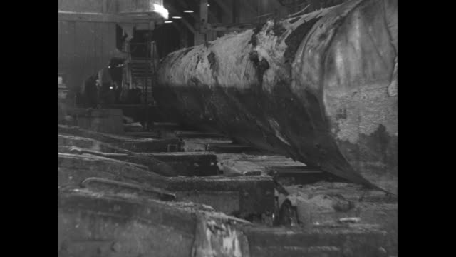 large log is rolled onto a conveyor and fixed by metal arms as a worker looks on / another log moves up a wooden u-shaped channel pulled by a chain /... - 材木置き場点の映像素材/bロール