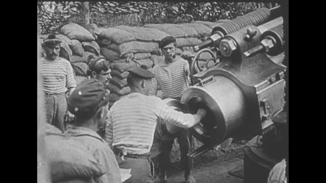 LS large long range gun at WWI battle front / MS gun crew packs firing material and missile into the gun and lowers it into position / cutaway muzzle...