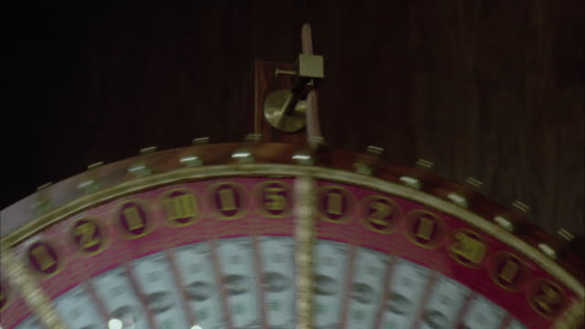 cu tu large lottery wheel spinning and stops at number five - lotterie stock-videos und b-roll-filmmaterial
