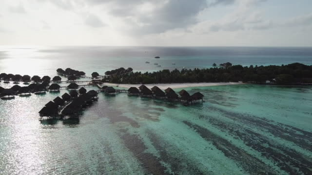 large luxurious overwater villas nestled in the turquoise blue lagoon - tourist resort stock videos & royalty-free footage