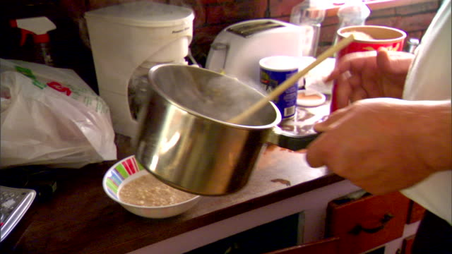 large male hand scooping contents out of angled pot into bowl, watery oatmeal. male placing pot back on stove. - oatmeal stock videos & royalty-free footage