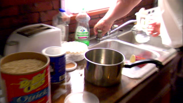 large male hands adding water to pot sitting on counter next to box of oatmeal flakes, measuring cut on counter, carrying pot toward stove. - oatmeal stock videos & royalty-free footage