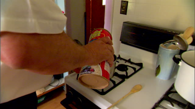 large male hands carrying box of oatmeal to pot on stove, pouring flakes in, - oatmeal stock videos & royalty-free footage