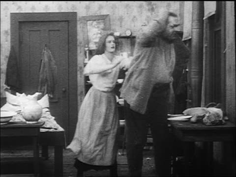 b/w 1917 large man (eric campbell) arriving home + shoving woman (janet miller sully) / they fight - conflittualità video stock e b–roll
