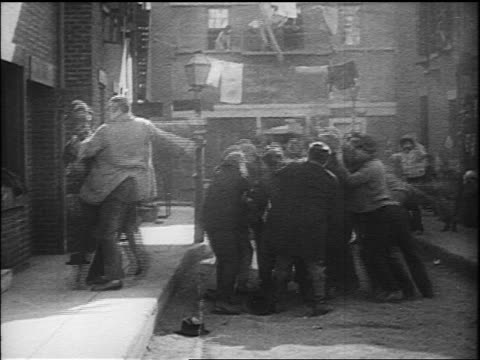 b/w 1917 large man (eric campbell) hits policeman (albert austin) + throws him into street fight - 1917 stock videos & royalty-free footage