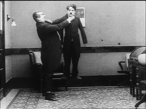 large man lifting charlie chaplin off of ground by neck walking offscreen - 1916 stock videos & royalty-free footage