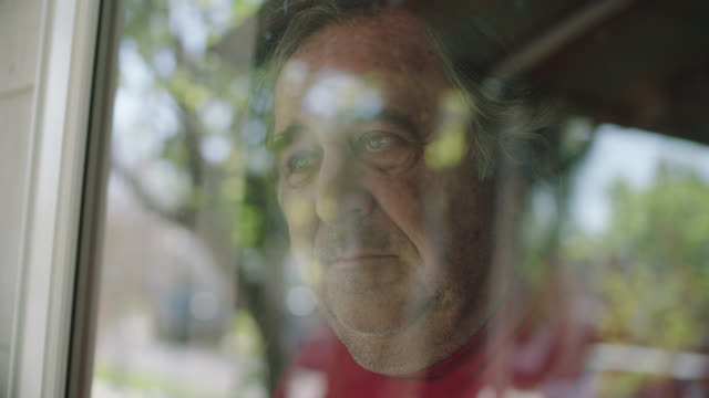 vídeos de stock e filmes b-roll de slo mo. cu of large man sadly looks out his window. - loneliness
