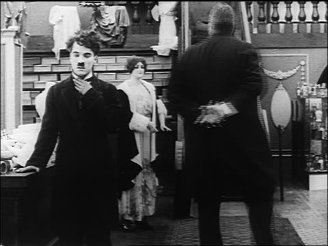 b/w 1916 large man strangles shakes chaplin / chaplin kicks him onto escalator - 1916 stock videos & royalty-free footage