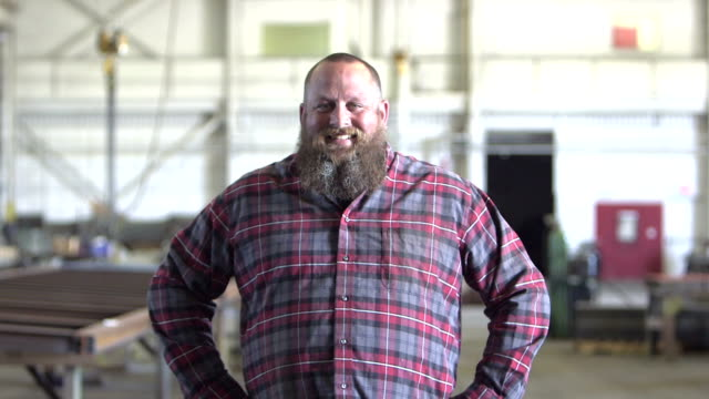 large man with beard in warehouse walks toward camera - barba peluria del viso video stock e b–roll