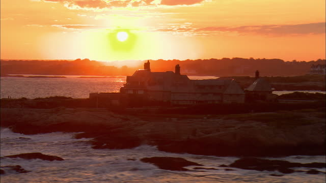 vídeos de stock, filmes e b-roll de low aerial, large mansion on rocky coast at sunset, newport, rhode island, usa - rhode island