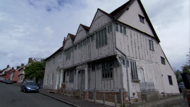 a large medieval house occupies a street corner in lavenham, england. available in hd. - lavenham stock-videos und b-roll-filmmaterial