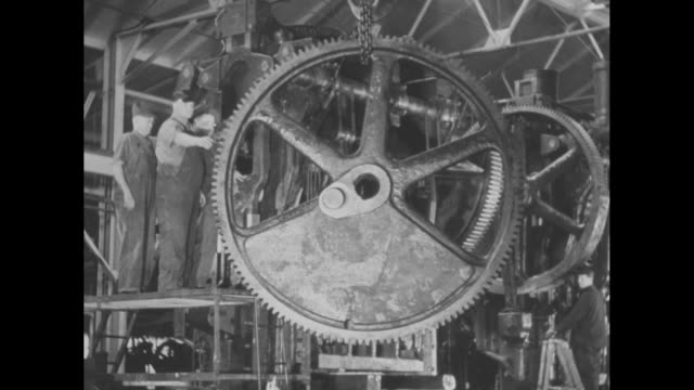 large metal cog wheel is lifted above a factory floor, positioned by workers, and pounded into place / note: exact month/day not known - postwar stock videos & royalty-free footage