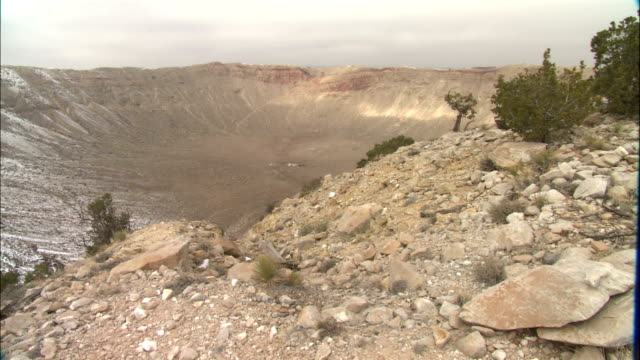 a large meteor crater shapes a desert landscape. - meteor crater stock videos & royalty-free footage