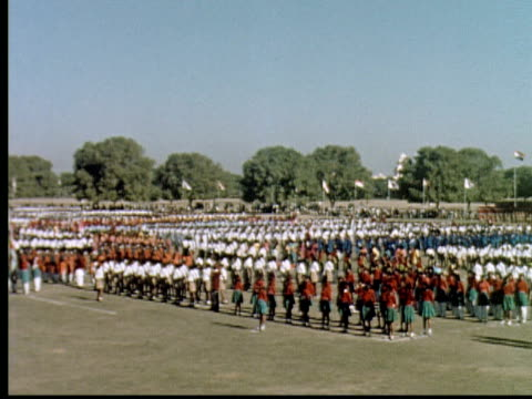 1960 montage large military review. groups stand in rows. children march in formation. crowd watches from bleachers / india - パレード点の映像素材/bロール