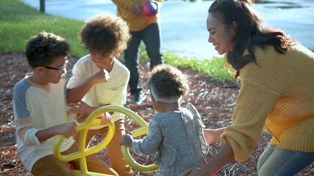 vídeos de stock e filmes b-roll de large mixed race family at playground on seesaw - família com quatro filhos