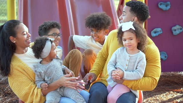 vídeos de stock e filmes b-roll de large mixed race family at playground on slides - família com quatro filhos