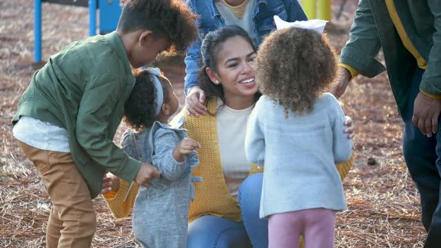 vídeos de stock e filmes b-roll de large mixed race family at playground, with pinwheels - família com quatro filhos