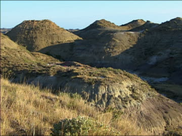 large mounds of earth cast in shadows / hell creek, montana - badlands stock videos & royalty-free footage