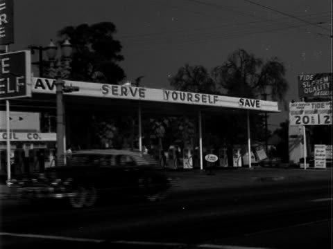 large multipump full service and self service gas station automobile traffic array of late 1930s and early 1940s roadsters early 1950s sedans passing... - 1951 stock videos & royalty-free footage