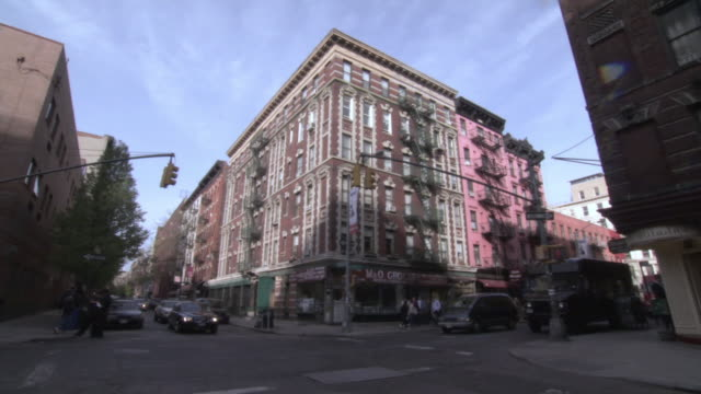 la large multi-unit apartment building on corner of busy intersection / new york, new york, united states - house rental stock videos & royalty-free footage