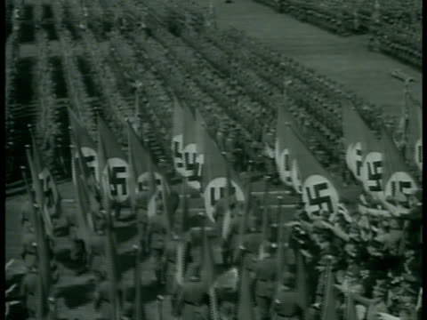 stockvideo's en b-roll-footage met large nazi flags flying on flagpoles top of building ha nazi rally in stadium nazi flag bearers walking on field between other soldiers ms people in... - 1938