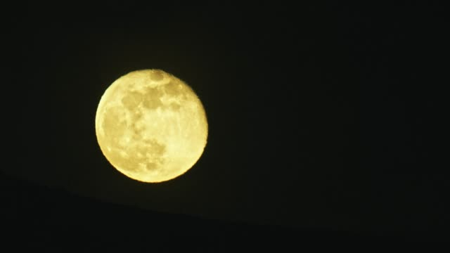a large, nearly full moon (waning gibbous) shines yellow in the night sky - meteor crater stock videos & royalty-free footage
