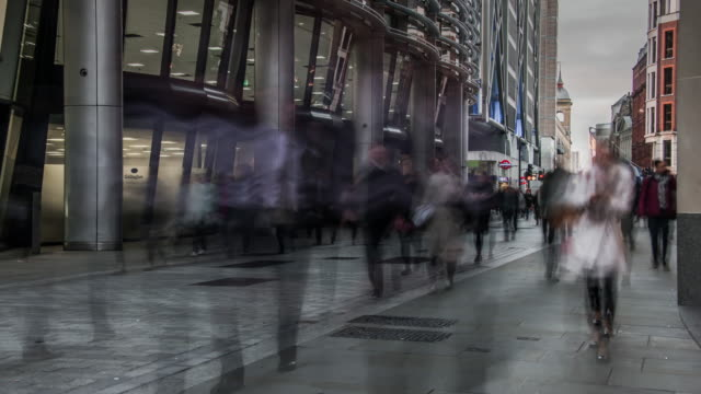 a large number of commuters move rapidly through a pedestrianised street in the city of london during the early morning rush hour - dringlichkeit stock-videos und b-roll-filmmaterial