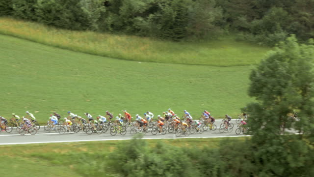 aerial large number of cyclists in a race through countryside - sports race stock videos and b-roll footage