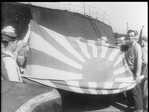 a large number of japanese sailors stand on the deck of the surrendered japanese battleship nagato with us troops / officers look at paperwork / us... - arrendersi video stock e b–roll