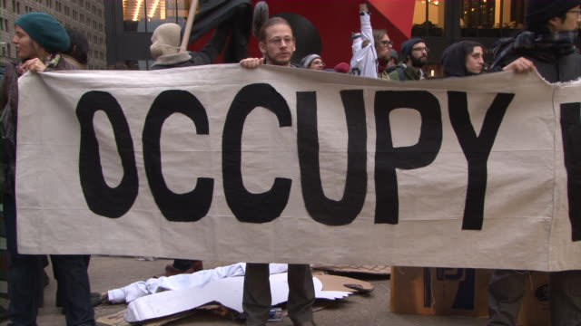 large occupy wall street sign holding up by protesters during occupy wall street movement audio / new york city, new york, united states - occupy protests stock videos & royalty-free footage