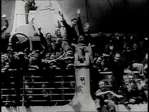 Large ocean liner steaming in harbor / Soldiers waving from ship's deck / Soldiers with duffel bags disembarking ship / People behind railing waiting...