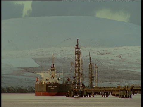 Large oil tanker docked at Sullom Voe refinery with snow covered hills in background, Shetland Islands