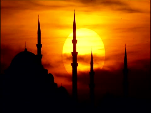 large orange sun sets behind minarets of hagia sophia (church of holy wisdom) istanbul - hagia sophia istanbul stock videos & royalty-free footage