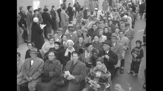 large outdoor audience of seated people wearing winter clothing / vs three men gathered around radio inside house / note: documentation incomplete - オーバーコート点の映像素材/bロール
