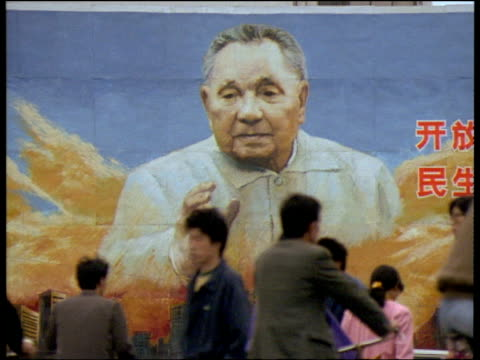 large painting of deng xiaoping on wall. soft focus chinese people cycle round in front of painting shenzhen china - 1994 stock videos and b-roll footage