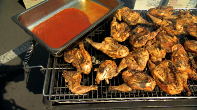 ms large pan w/ barbeque sauce on edge of long charcoal grill half chickens grilling bbq barbeque food cooking meat - bbq sauce stock videos and b-roll footage