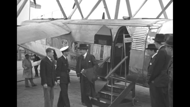 large passenger biplane taxis toward two men with luggage carts / a man deplanes and is greeted by several dignitaries and military officers / note:... - passenger stock videos & royalty-free footage