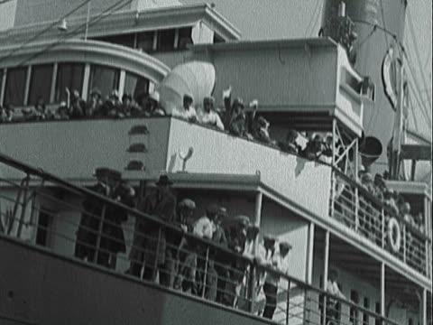 montage large passenger liner pulling into port and crowds waving / new york, new york, united states - passagier wasserfahrzeug stock-videos und b-roll-filmmaterial