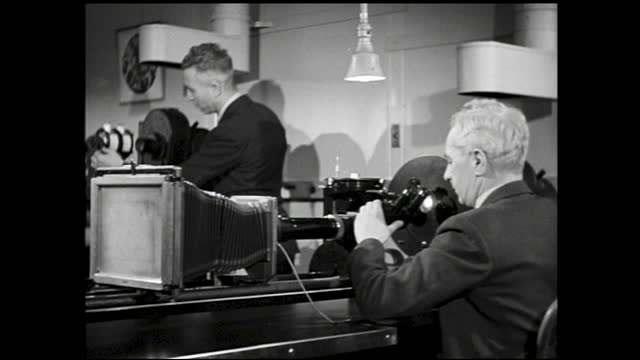 large piece of crystal being measured and examined; man looking through microscope-like machine; men working inside laboratory looking into machine... - 1940 1949 stock videos & royalty-free footage