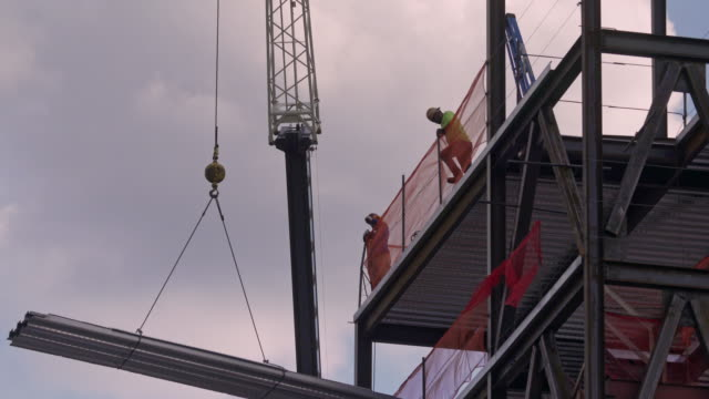 A large piece of sheet metal is raised up a construction site.