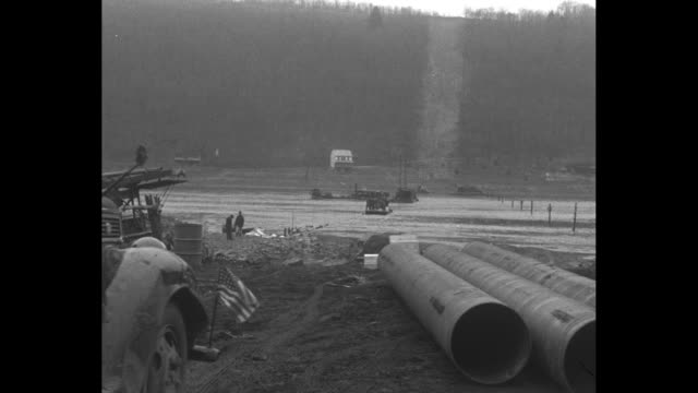 large pile of stenciled dynamite crates / a working pump in the foreground with the path of the pipeline cutting up a hill beyond / men with 24-inch... - 起爆装置点の映像素材/bロール