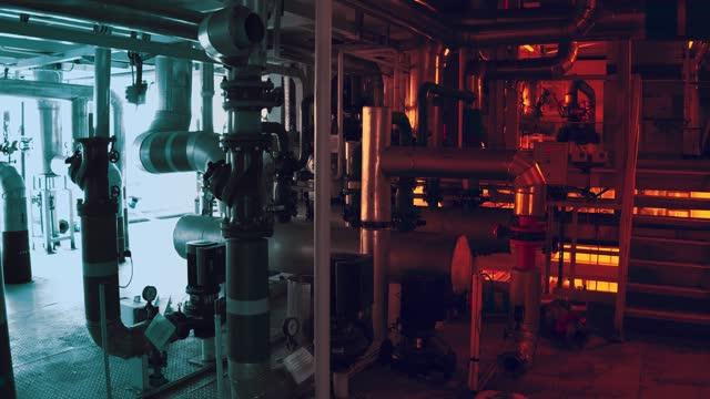 vidéos et rushes de grands tuyaux dans une usine dans l'éclairage rouge - pression physique