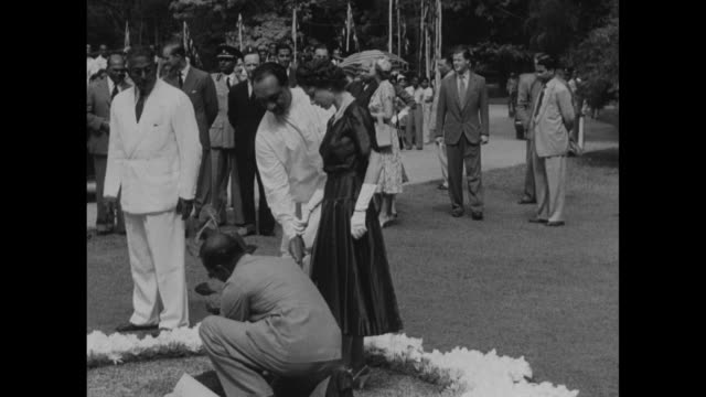 stockvideo's en b-roll-footage met large plant in ornate pot / man takes cutting out of box as elizabeth ii and others look on / man presents potted small plant to queen / men and... - sri lankaanse cultuur