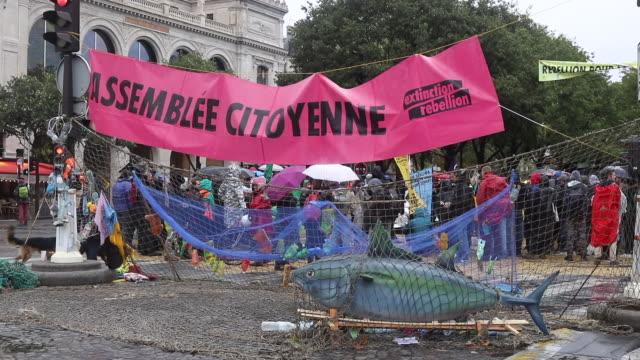 vidéos et rushes de large plastic fish caught in a net with plastic waste on the change bridge false tuna a banner citizen assembly the activists of the ecologist... - rébellion