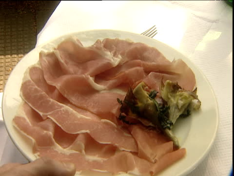 Large plate of Parma ham with green vegetable garnish is placed on table at alfresco restaurant