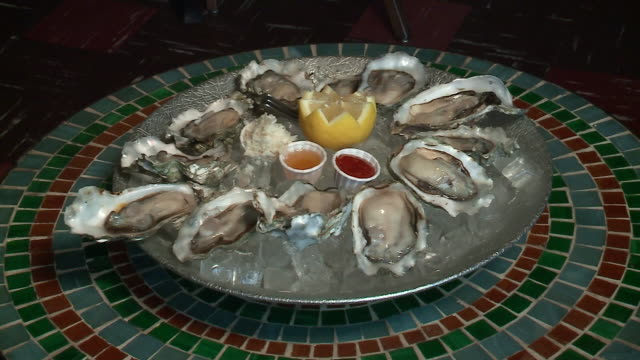 wgn large platter of oysters on ice with lemon and sauces at café mariejeanne in chicago on may 9 2017 - råmaterial bildbanksvideor och videomaterial från bakom kulisserna